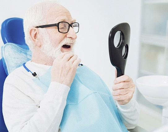 Older man checking teeth and stroking beard