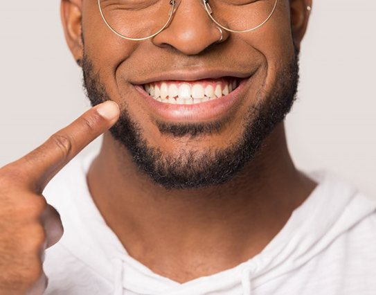 man pointing to his smile after getting dental bonding in Little Rock