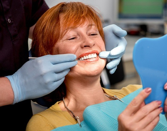 Woman at preventive dentistry visit to avoid the need for emergency dental care
