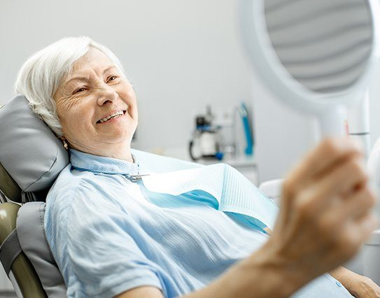 Older woman in dental office looking at smile with new dental bridge