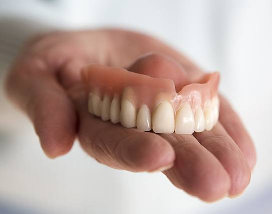 Hand holding a full removable denture