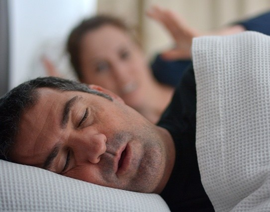 Frustrated woman next to snoring man in need of sleep apnea therapy
