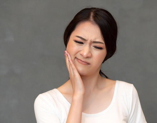 A young woman cringing and holding her jaw in discomfort